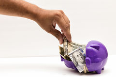 Taking my Savings. A hand taking money from a piggy Stock Photography