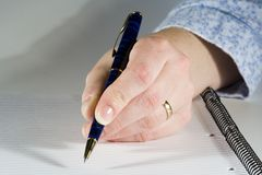 Taking Note. Hand holding a pen getting ready to write a note on a spiral bound pad Royalty Free Stock Images