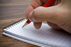 Taking note. Writing on a notepad with a pencil royalty free stock images