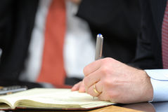 Taking notes at board meeting. Hand detail of businessman tanking notes at board meeting Royalty Free Stock Photos
