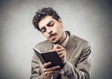 Taking notes. A concentrated businessman taking notes Stock Image