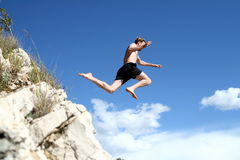 Taking Off. A young man jumps from a cliff into the sea Stock Photography