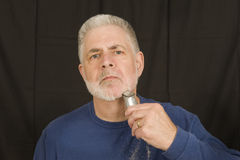 Taking Off The Beard. A middle aged man continues the process of shaving off his beard Royalty Free Stock Photography