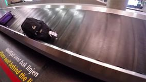 Taking off backpack from airport belt in Oslo Norway. Taking off black backpack from airport belt in Oslo Norway stock footage