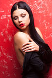Taking off her clothing. Beautiful young woman taking off her dress and looking away while standing against red background Stock Image