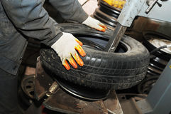 Taking off tyre from car wheel disc Royalty Free Stock Photo