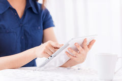 Taking opportunity of free Wi-Fi. Close-up of woman using digital tablet while sitting at the table with cup of hot drink on it Stock Images