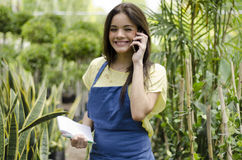 Taking an order from a customer. Cute female gardener taking an order from a customer on the phone Stock Photography