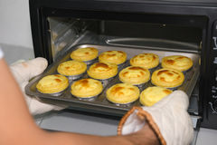 Taking out egg tarts from oven Royalty Free Stock Image