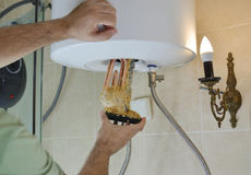 Taking out an old water heater. Plumber taking out an old water heater with scale deposition from a boiler in a bathroom stock photos