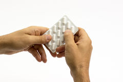 Taking out pill from blister pack Stock Photos