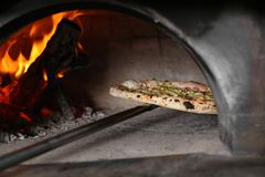 Taking out tasty pizza from oven in kitchen stock photography