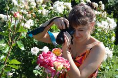 Taking photo. A young woman takes a photography of a flower, in the middle of a garden Royalty Free Stock Photo