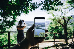 Taking photo of beautiful landscape at the M. Hand and smartphone taking photo of beautiful landscape at the Monte Barro with a girl on the foreground. Lomardy stock images