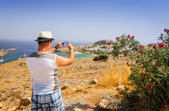Taking photo of beautiful Rhodes landscape. Man taking mobile photo in vacation scenery stock image