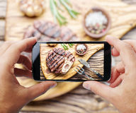 Taking photo of beef steak by smartphone. Royalty Free Stock Photo