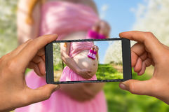 Taking photo of belly of a pregnant girl with mobile phone royalty free stock photos