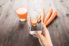 Taking photo of carrot juice on wooden background Royalty Free Stock Image