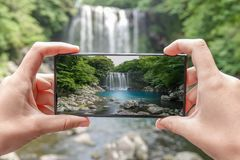 Taking Photo of Cheonjeyeon Waterfall on Jeju Island, South Korea with Mobile Phone. Active Tourism in Asia Stock Photo