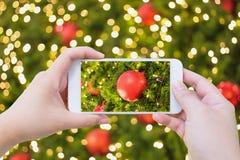 Taking photo of Christmas decoration on christmas tree Stock Photo