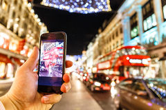 Taking photo of Christmas London on mobile phone Stock Image
