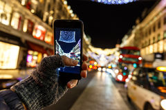 Taking photo of Christmas London on mobile phone Royalty Free Stock Image