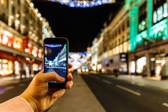Taking photo of Christmas London on mobile phone Royalty Free Stock Photos