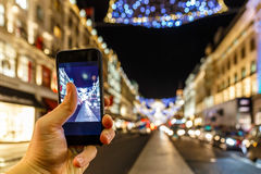 Taking photo of Christmas London on mobile phone Royalty Free Stock Images