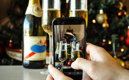 Taking a photo of a Christmas tree and champagne glasses with a smartphone royalty free stock image