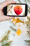 Taking photo of Christmas tree decoration outdoors. Travel concept - tourist taking photo of Christmas tree decoration outdoors on mobile gadget Stock Images