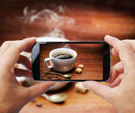 Taking photo of cup of coffee by smartphone. Royalty Free Stock Images