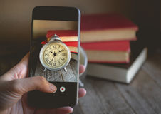Taking a photo by Finger Pressing on Cellphone for Photograph Roman Numeral in Vintage Alarm Clock and Stack of Book with Copy Sp. Ace. Image for Advertise about royalty free stock photography