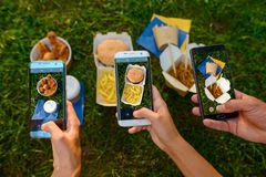 Taking photo of food. On the grass. Chicken nuggets, burger, French fries and wok, stir-fried dles. Mania of food photography concept royalty free stock images
