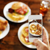 Taking photo of food with smartphone. At dinner table royalty free stock photo