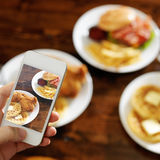 Taking photo of food with smartphone. Shot close up with selective focus Stock Photo