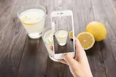 Taking photo of freshly squeezed lemon juice in glasses. Stock Photos