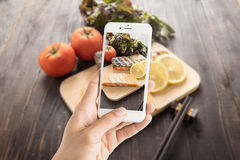Taking photo of grilled salmon on cutting board on wooden backgr Stock Images