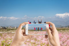 Taking photo of hiker cheering elated and blissful with arms rai. Sed in the sky Stock Images