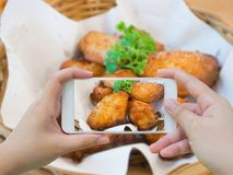 Taking photo of hot and spicy chicken wings with smartphone. Woman taking photo of hot and spicy chicken wings in basket with mobile smartphone royalty free stock photo