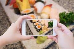 Taking photo of Japanese sushi set Royalty Free Stock Image