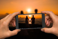 Taking photo of loving couple at sunset with mobile phone Stock Photo