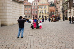 Taking a photo. Man takes a photo of his family in the old square of Poznan, Poland Stock Images
