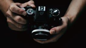 Taking photo. Hands holding photo camera on black background Royalty Free Stock Photography