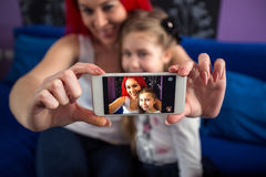 Taking photo with mobile phone mom and daughter. Having fun royalty free stock photo