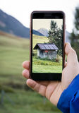 Taking photo of a mountain hut with smartphone. Taking photo of a wooden cabin with cell phone Royalty Free Stock Photography
