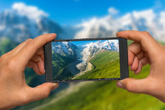 Taking photo of mountains and glacier with mobile phone stock photo