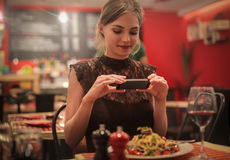 Taking a photo of the pasta. Woman is taking a photo of the pasta Royalty Free Stock Image