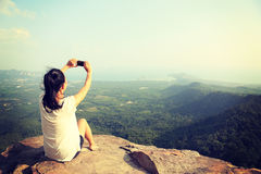 Taking photo with smart phone at mountain peak cliff Royalty Free Stock Photography