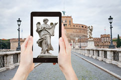 Taking photo of statue on St Angel Bridge, Rome Stock Images