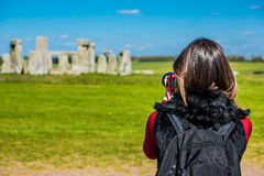 Taking a photo of Stonehenge. A young girl looking at the stones in Stonehenge and taking a photo with her camera royalty free stock photo